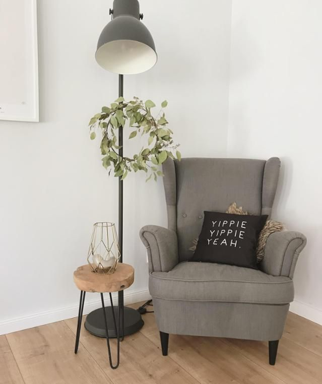 Cozy wing chair with standard lamp and wooden side table. Community With …