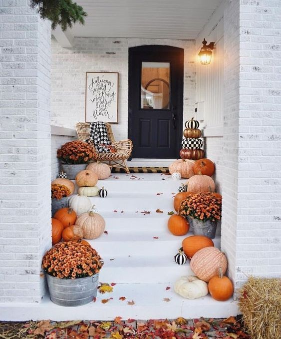 Fall decorations for an entryway with pumpkins, leaves, and wall decoration.
