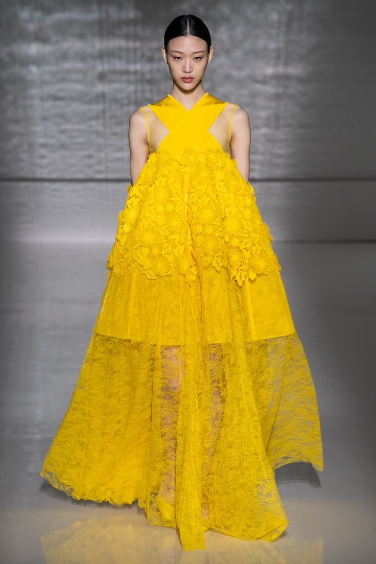 A model walks the runway wearing a bright yellow lace gown for the Givenchy haut…